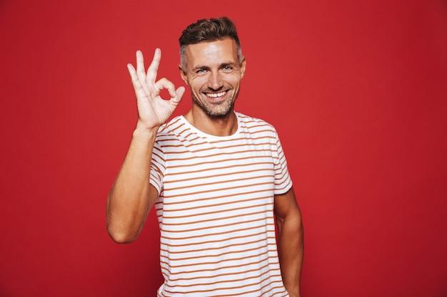 Брюнетка молодой человек в полосатой футболке улыбается и показывает знак ок, изолированные на красном