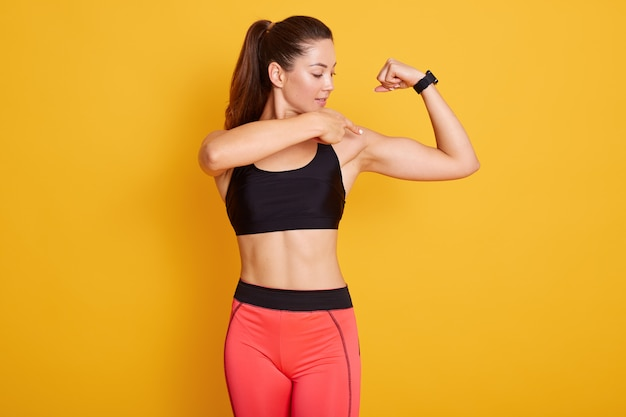 Brunette young woman dresses black top and leggins, pointing at her bicep.