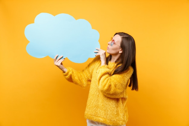 Brunette young woman in heart eyeglasses looking on empty blank blue say cloud speech bubble in hands isolated on bright yellow background. people sincere emotions lifestyle concept. advertising area.