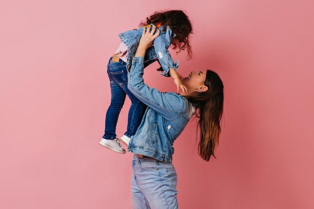 Брюнетка молодая женщина, держащая дочь на розовом фоне. студийный снимок мамы и подростка в джинсовых куртках.
