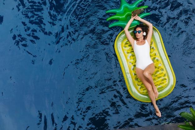 プールで泳いでいる間音楽を聞いている白い水着のブルネットの若い女性。夏のリゾートで楽しんでいる魅惑的な黒髪の女性の屋外写真。