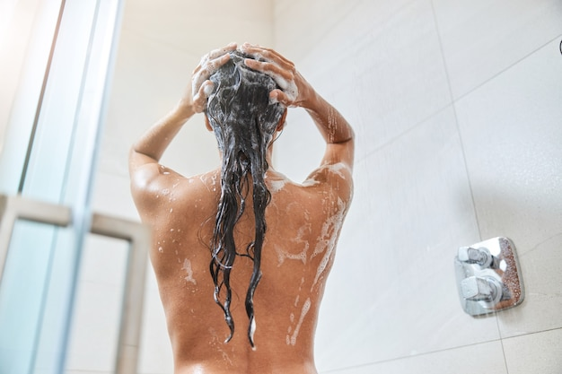 Брюнетка молодая женщина, моющая длинные волосы в душе