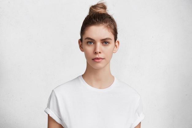 Giovane donna castana in maglietta bianca