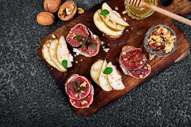 Брускетта и кростини с грушей, сыром рикотта, медом, инжиром, орехами и зеленью.