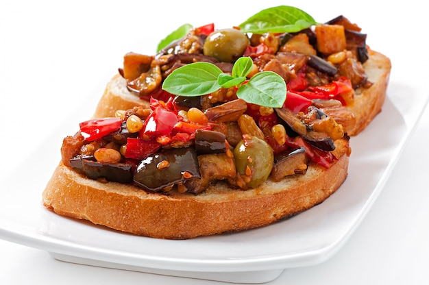 Bruschetta caponata with raisins and pine nuts decorated with a leaf of basil