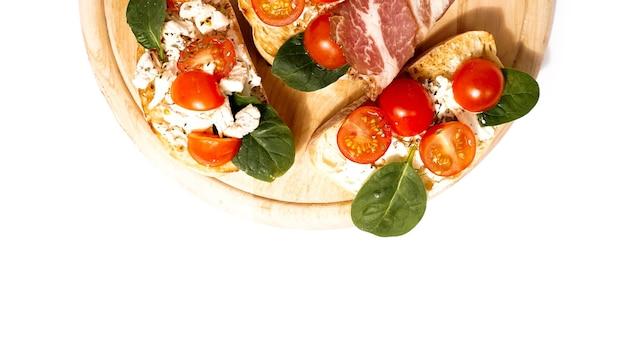 Брускетту обычно подают как закуску или итальянскую закуску на деревянной доске.