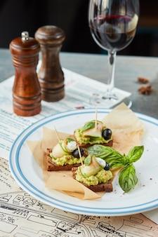 흰색 접시와 레드 와인 한 잔에 있는 나무 테이블에 브루스케타