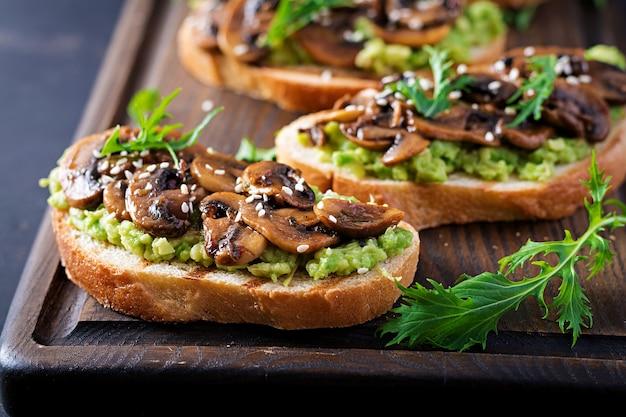 Брускетта. бутерброд с авокадо, жареными грибами, кунжутом на деревянной доске.