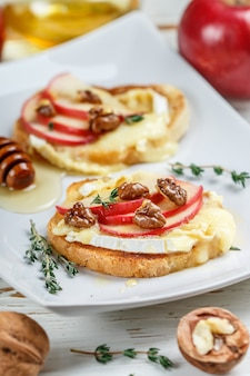 Bruschetta sandwiches with brie or camembert cheese, apples, walnuts, thyme and honey
