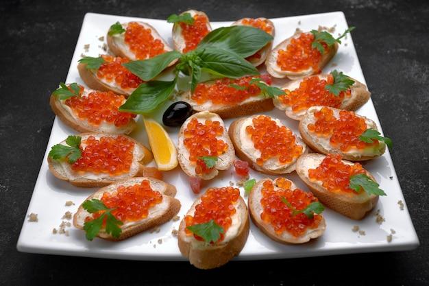 Брускетта, бутерброды с красной икрой лосося, на белой тарелке, крупным планом, малая глубина резкости. оформление банкетов, кейтеринг. жирный