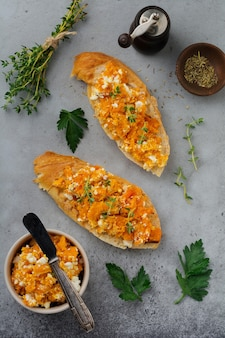Bruschetta with baked pumpkin, feta cheese and thyme on gray concrete surface