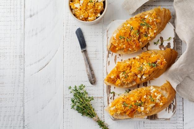Bruschetta with baked pumpkin, feta cheese and thyme on light wooden background spicy pumpkin sandwich