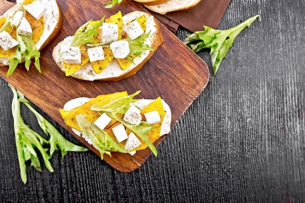 焼きカボチャ、塩味のフェタチーズ、リコッタチーズ、ルッコラとスパイス、上から木の板の背景にタオルとブルスケッタ