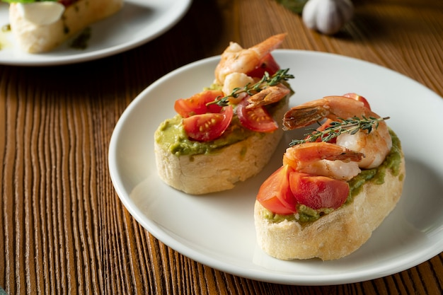Bruschetta with bell shrimp, avocado, pesto sauce and cherry tomato on a white plate on a wooden background. italian restaurant. close up food photo