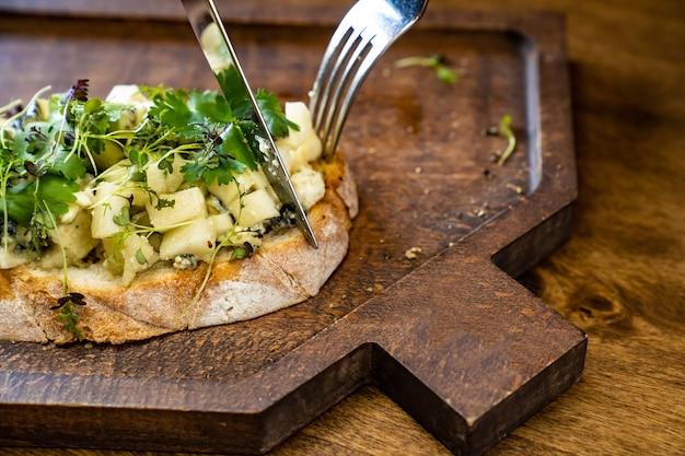 사진과 비디오 촬영을 위한 칼과 포크가 있는 나무 커팅 보드에 치즈와 채소를 곁들인 브루스케타. 푸드스타일리스트와 사진작가로 일한다. 레스토랑 메뉴와 카페