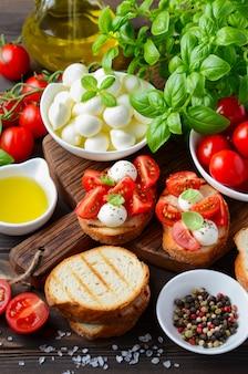 Bruschetta with cherry tomatoes and mozzarella on dark wooden table.