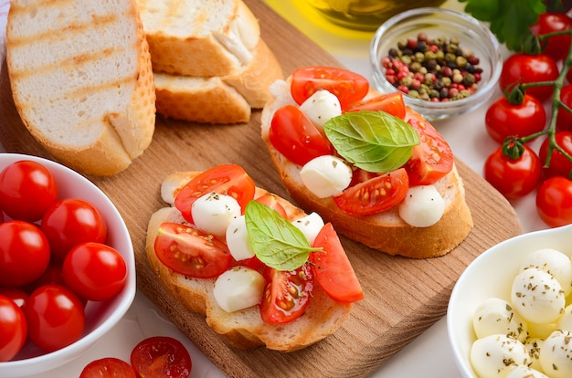 Bruschetta with cherry tomatoes and mozzarella on wooden cutting board.