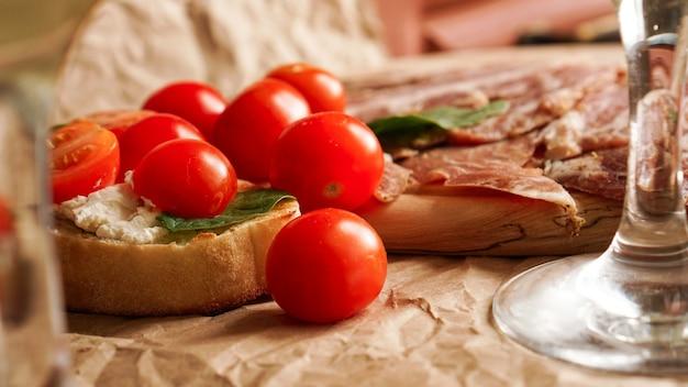 チェリートマトのブルスケッタ。ワイングラス、イタリアの前菜。クラフト紙の背景。ピクニックの概念