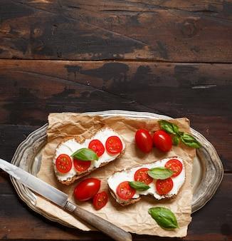 木製のテーブルにクリームチーズ、チェリートマト、バジルのブルスケッタ