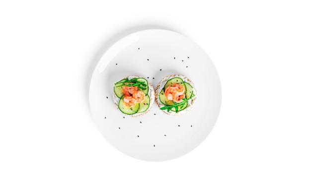 Брускетта со сливочным сыром, креветками, огурцом и листьями рукколы изолированы. тост изолирован. сэндвич изолирован. сэндвич с креветками, лососем и сыром