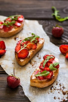 Bruschetta with cream cheese, strawberry, arugula and balsamic vinegar sauce with honey. c