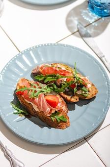 Брускетта с темным багетом, хамоном, рукколой и помидорами на белом плиточном столе, яркий жесткий солнечный свет. здоровая и стильная закуска.