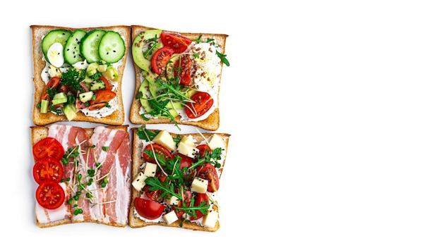 Брускетта с разными начинками на белом фоне. брускетта из овощей, мяса и сыра. фото высокого качества