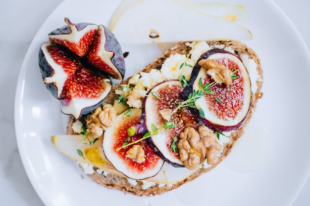 Bruschetta with figs, walnuts, honey and goat cheese, top view