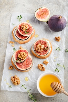 Bruschetta with fresh ricotta cheese, figs, nuts, thyme and honey on gray concrete.