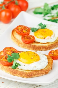 Bruschetta with fried egg, tomatoes and herbs