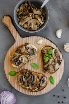 Bruschetta with fried mushrooms with onion, garlic, thyme and basil on a cutting board on a dark concrete background. vertical orientation.