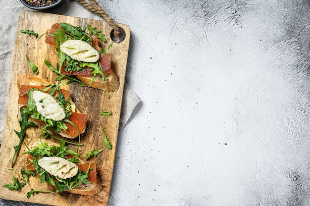 Bruschetta with goat cheese, arugula and pear marmalade. gray background