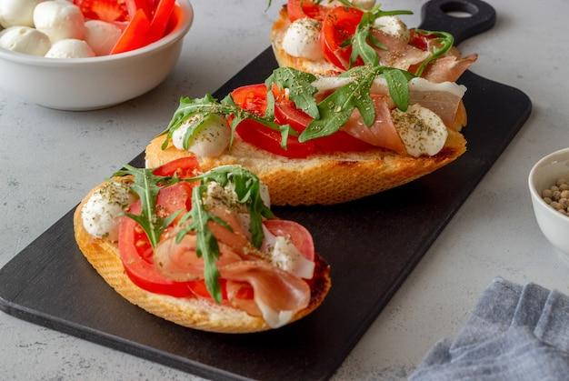Bruschetta with ham, mozzarella, tomatoes and arugula. wine appetizer. snack.