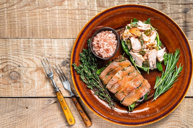 Bruschetta with hot and cold smoked salmon, arugula, capers on a rustic plate with herbs. wooden background. top view. copy space.