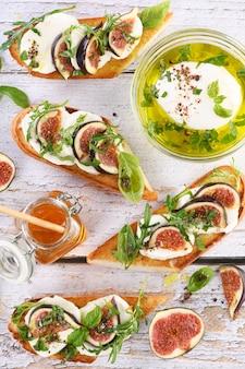 꿀과 향신료로 맛을 낸 모짜렐라, 루꼴라, 무화과를 곁들인 브루스케타