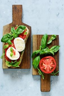 木製のダイニングボードにモッツァレラバッファローチーズのブルスケッタとルッコラの葉と灰色の壁にオリーブオイルとバジルのトマトサルサの葉。昼食。ランチスナック、イタリアン