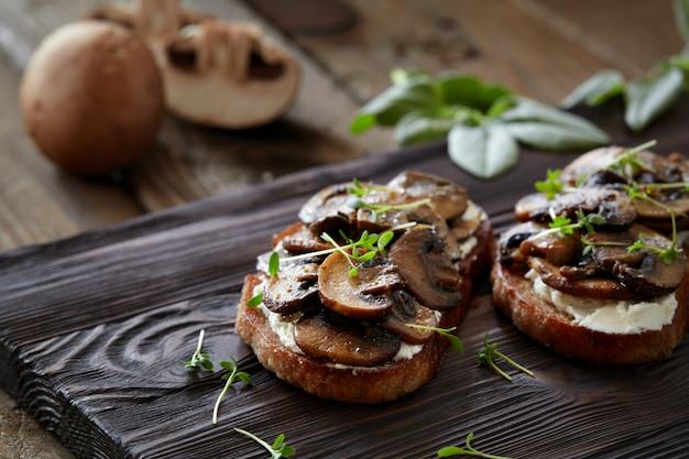 キノコと素朴な木製の背景にクリームチーズのブルスケッタ