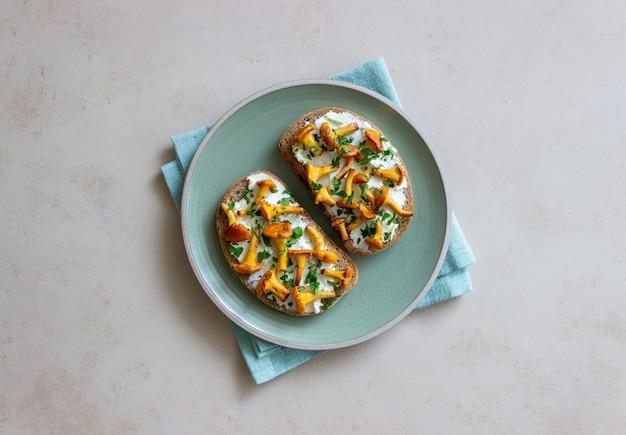 キノコのアンズタケとホワイトチーズのブルスケッタ。健康的な食事。ベジタリアンフード。