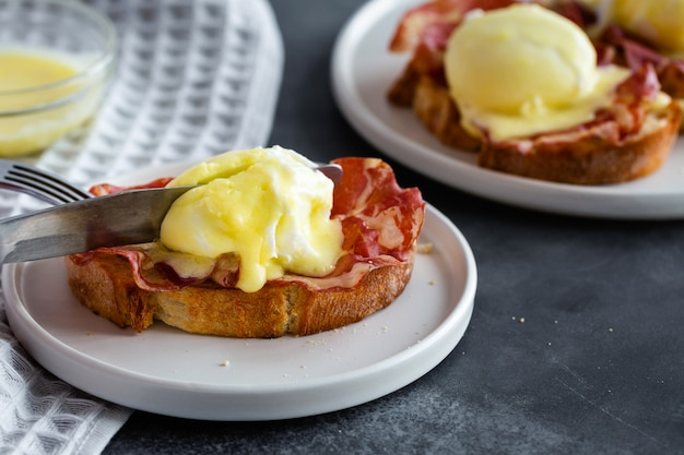 Bruschetta with parma ham and egg benedict, classic eggs benedict with bacon, hollandaise sauce, english breakfast with tasty toasts