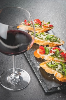Bruschetta with pesto, parmesan, tomatoes and basil on tray with wine