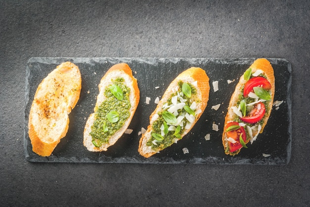 Bruschetta with pesto, parmesan, tomatoes and basil on tray