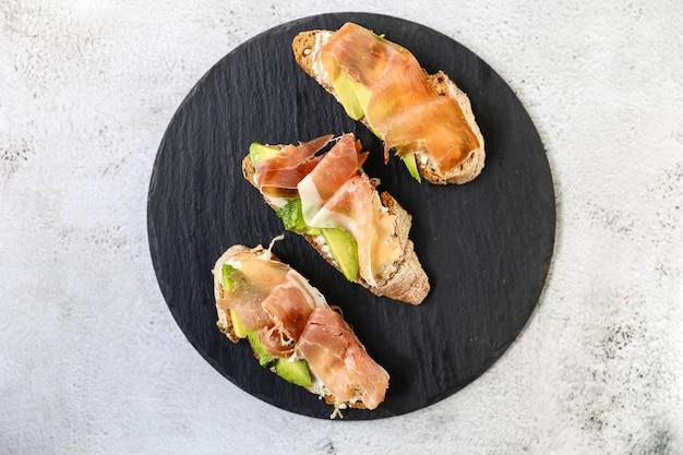 Брускетта с прошутто, сливочным сыром и микрогринами. хлеб с копченым беконом и сливочным сыром.