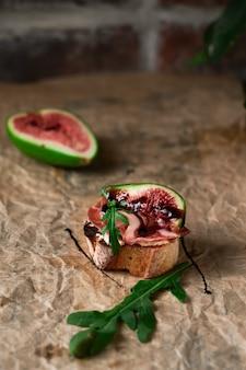 Брускетта с ветчиной прошутто, сыром рикотта, рукколой и свежим инжиром на темной бумаге