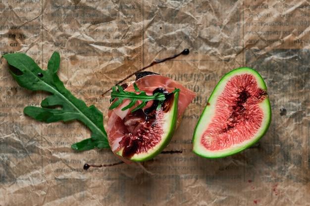 Bruschetta with prosciutto ham, ricotta cheese, arugula and fresh figs on a dark paper