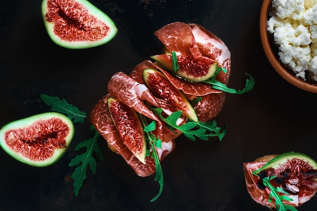 Bruschetta with prosciutto ham, ricotta cheese, arugula and fresh figs on a dark vintage tray.