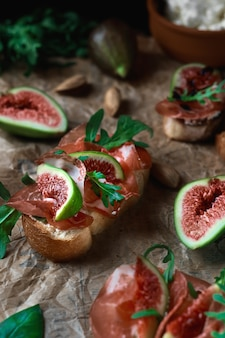 Bruschetta with prosciutto ham, ricotta cheese and fresh figs on a sheet of paper.