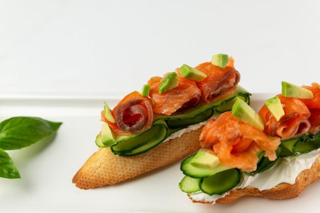 Брускетта с красной рыбой и свежим огурцом на тарелке. аппетитная закуска. белый фон. место для текста.