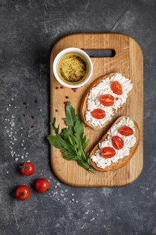 Bruschetta with roasted tomatoes and mozzarella cheese on a cutting board
