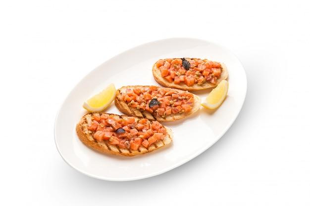 Брускетта с лососем и авокадо, ржаной багет, сливочный сыр, лосось, икра тобико, авокадо, базилик. изолированное изображение на белом