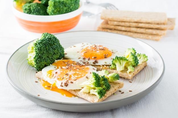 곡물에 으깬 계란과 브로콜리를 곁들인 브루스케타 참깨와 아마씨를 곁들인 빵과 테이블에 브로콜리 한 그릇